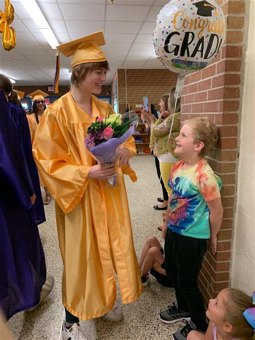 Senior Madelyn Wagner receives bouquet from Kindergardener-brother Miles